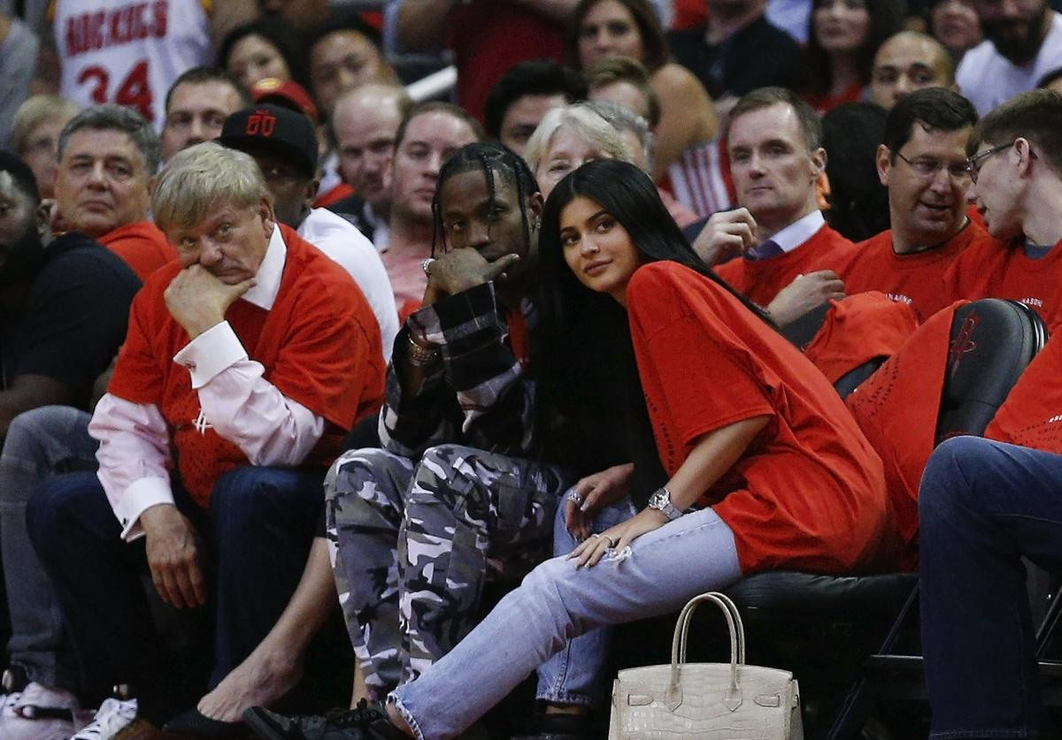 Travis Scott and Kylie Jenner watch a game courtside