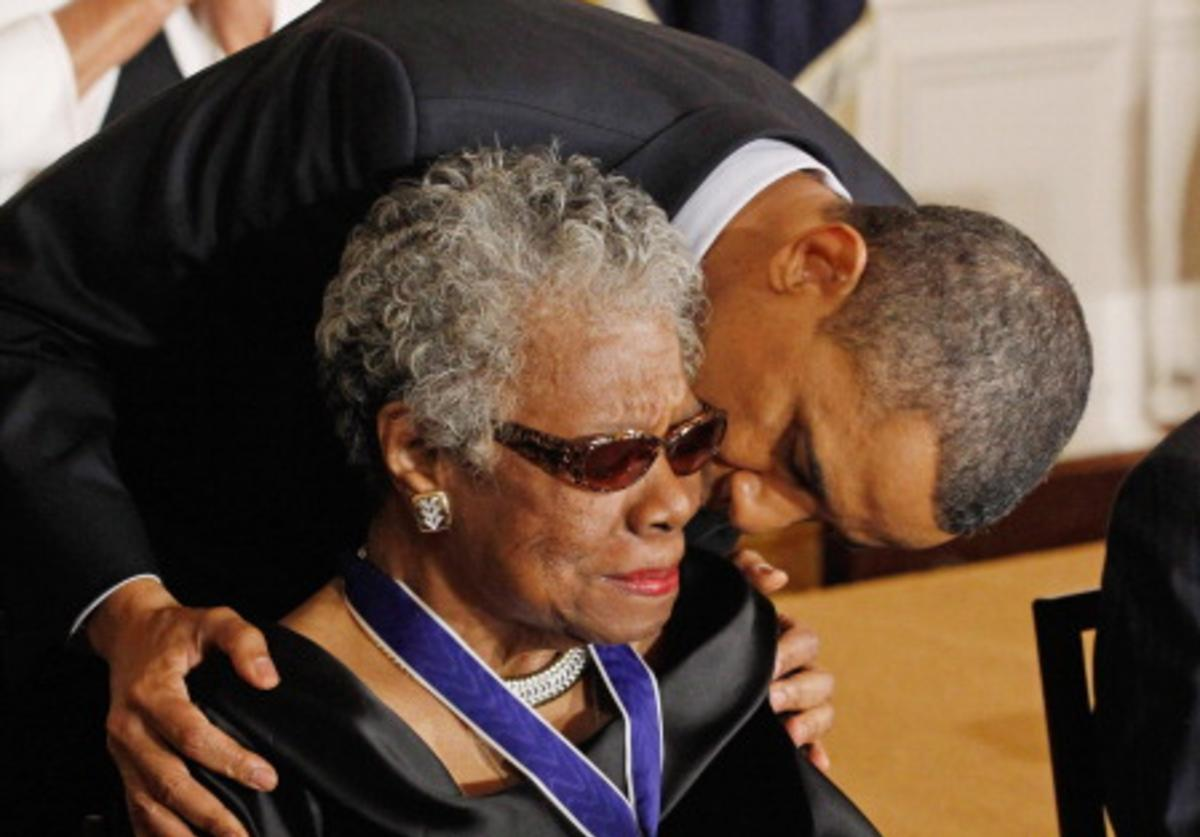 President Barack Obama (R) kisses poet and author Maya Angelou after giving her the 2010 Medal of Freedom in the East Room of the White House February 15, 2011 in Washington, DC.