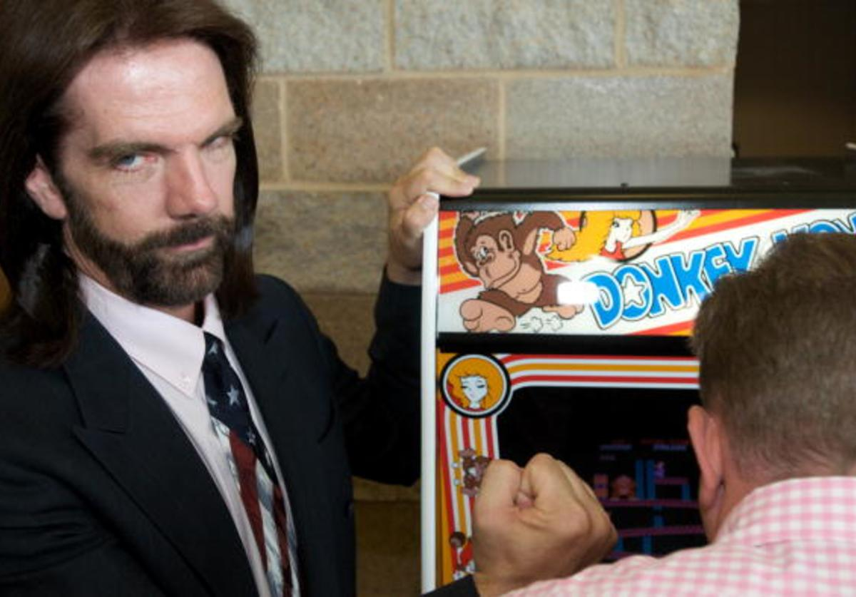 Billy Mitchell, the Video Game Player of the Century, poses while Steve Sanders, 'The Orignal King of Kong,' plays Donkey Kong at the launch party for the International Video Game Hall of Fame and Museum on August 13, 2009 in Ottumwa, Iowa.