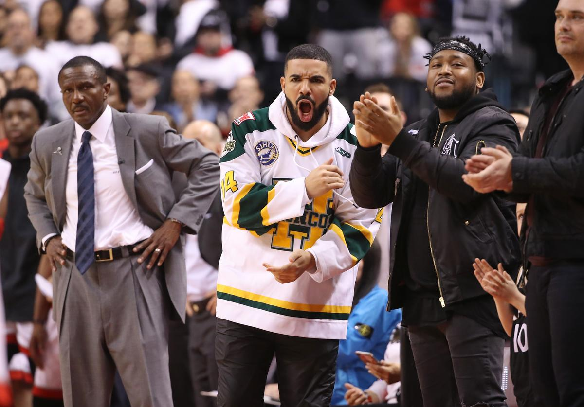 Drake celebrates as head coach Dwane Casey of the Toronto Raptors looks on in the closing moments of their victory against the Washington Wizards in the first quarter during Game One of the first round of the 2018 NBA Playoffs at Air Canada Centre on April 14, 2018 in Toronto, Canada