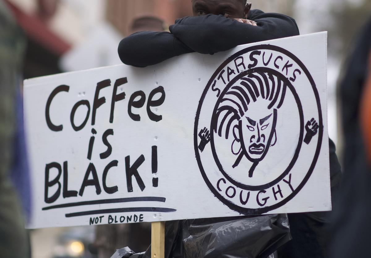 Protestor Jack Willis, 26, (C) demonstrates outside a Starbucks on April 15, 2018 in Philadelphia, Pennsylvania. Police arrested two black men who were waiting inside a Center City Starbucks which prompted an apology from the company's CEO.