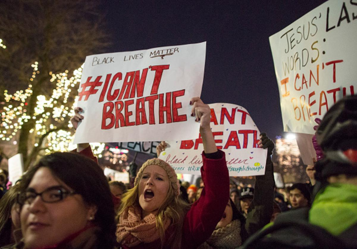 Protesters march while chanting and holding signs during a protest against the decision by a Staten Island grand jury not to indict a police officer who used a chokehold in the death of Eric Garner in July, on December 4, 2014 in Boston, Massachusetts.