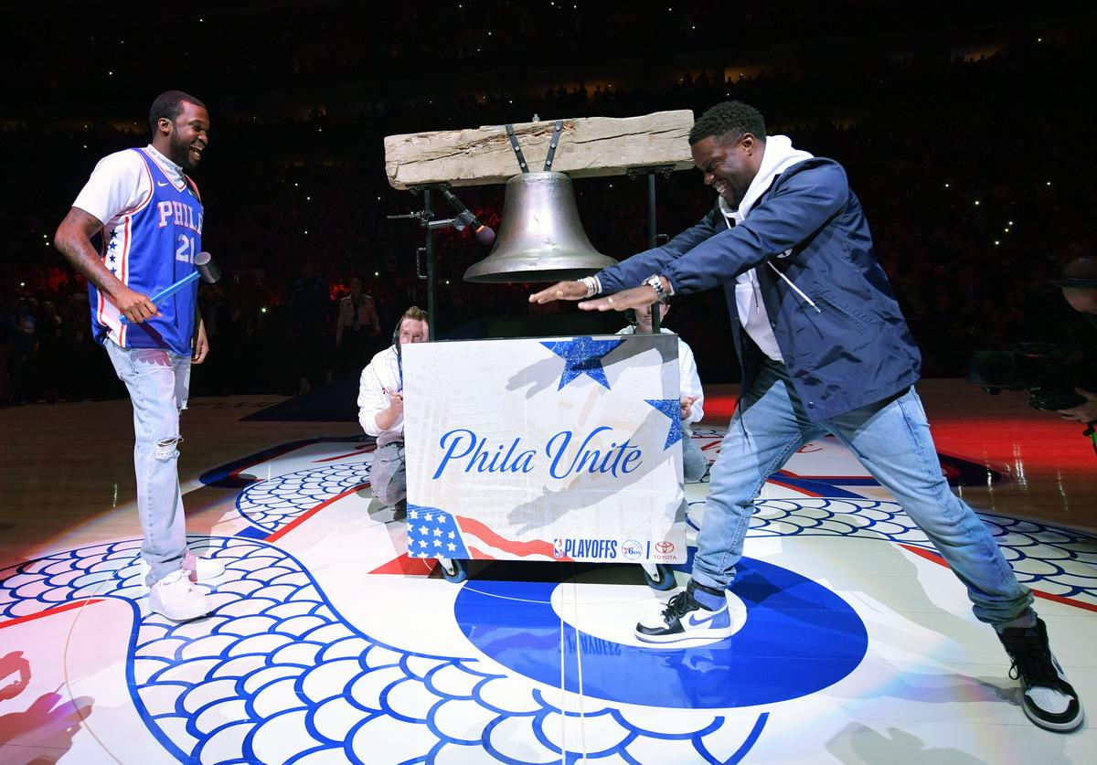 Meek Mill laughs as Kevin Hart bows to him before ringing a replica Liberty Bell at Wells Fargo Center on April 24, 2018 in Philadelphia, Pennsylvania