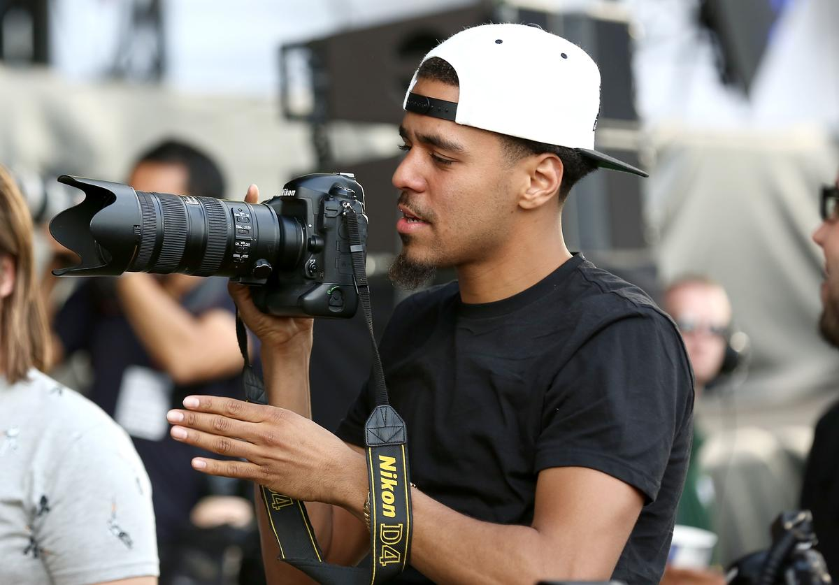 J Cole borrows a photographer's camera in the photo pit during the Outkast performance stage at Wireless Festival at Finsbury Park on July 6, 2014 in London, United Kingdom