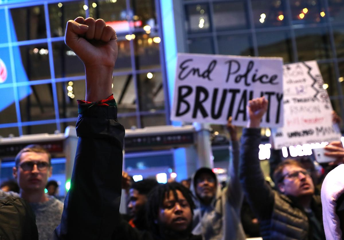 Black Live Matter protesters hold their fists in the air as they block the entrance to the Golden 1 Center during a demonstration on March 22, 2018 in Sacramento, California. Hundreds of protesters staged a demonstration against the Sacramento police department after two officers shot and killed Stephon Clark, an unarmed black man, in the backyard of his grandmother's house following a foot pursuit on Sunday evening.