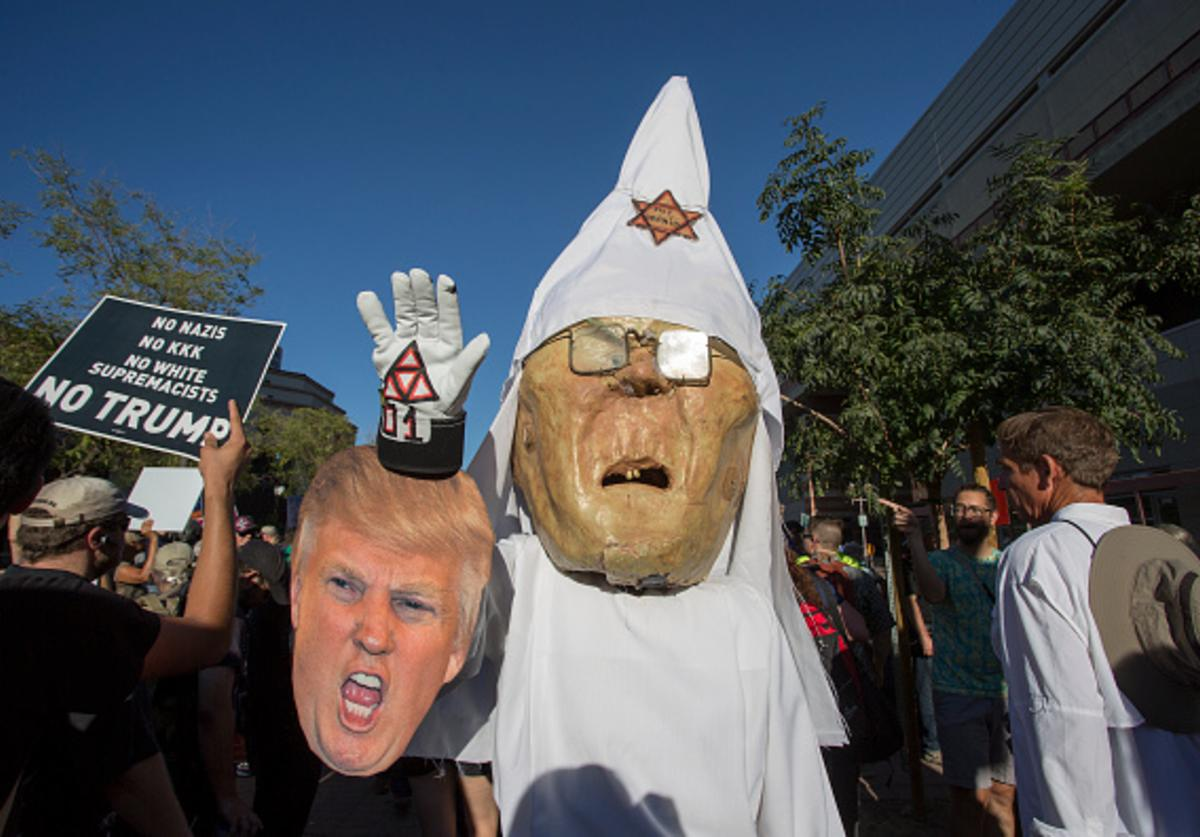 A protester wears a costume likeness of Sheriff Joe Arpaio as a member of the KKK with a characture picture of President Trump outside the Phoenix Convention Center at a rally by President Donald Trump on August 22, 2017 in Phoenix, Arizona.