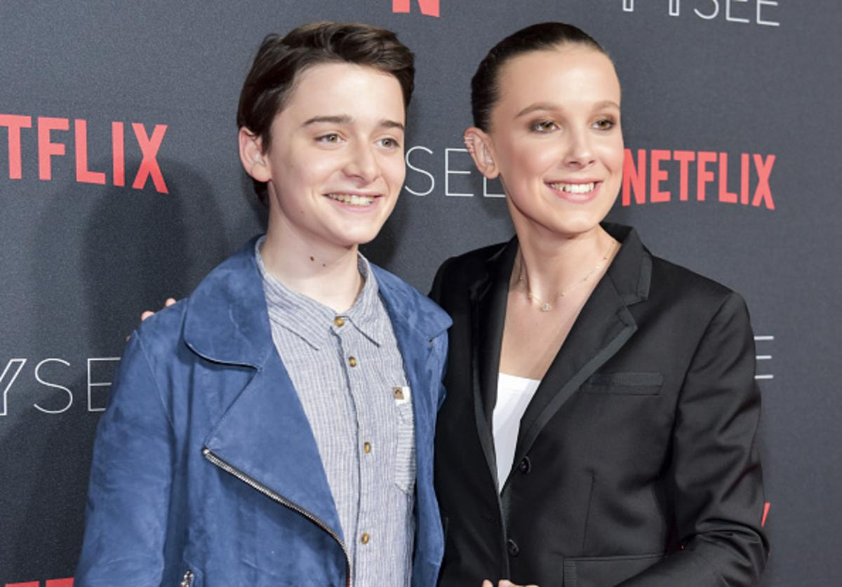 Actress Millie Bobby Brown (R) and Noah Schnapp arrive at the #NETFLIXFYSEE event for 'Stranger Things' at Netflix FYSEE at Raleigh Studios on May 19, 2018 in Los Angeles, California.