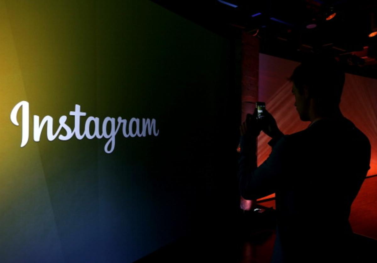 An attendee takes a photo of the instagram logo during a press event at Facebook headquarters on June 20, 2013 in Menlo Park, California.