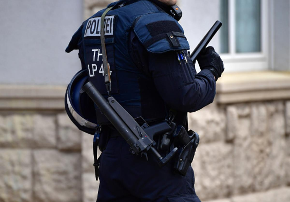A police officer with a tear canister gun walks by supporters of the far-right NPD political party while marching on May Day on May 1, 2018 in Erfurt, Germany.