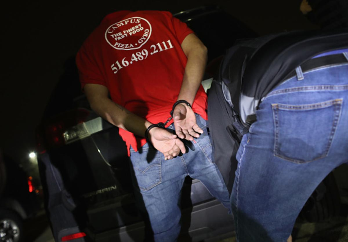 U.S. federal agents arrest a suspected gang member late on March 28, 2018 in Hempstead, New York.