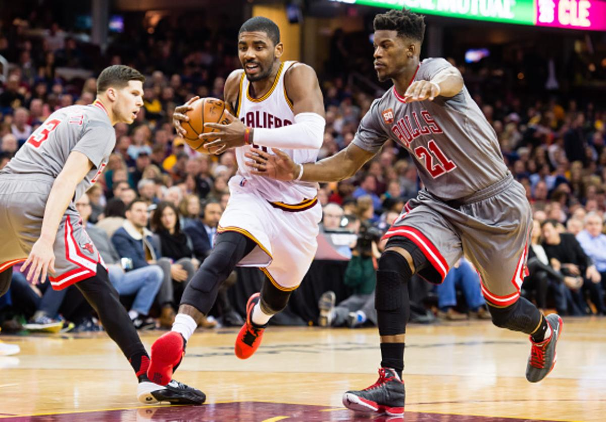 Kyrie Irving #2 of the Cleveland Cavaliers drives through Doug McDermott #3 of the Chicago Bulls and Jimmy Butler #21 during the first half at Quicken Loans Arena on January 23, 2016 in Cleveland, Ohio.