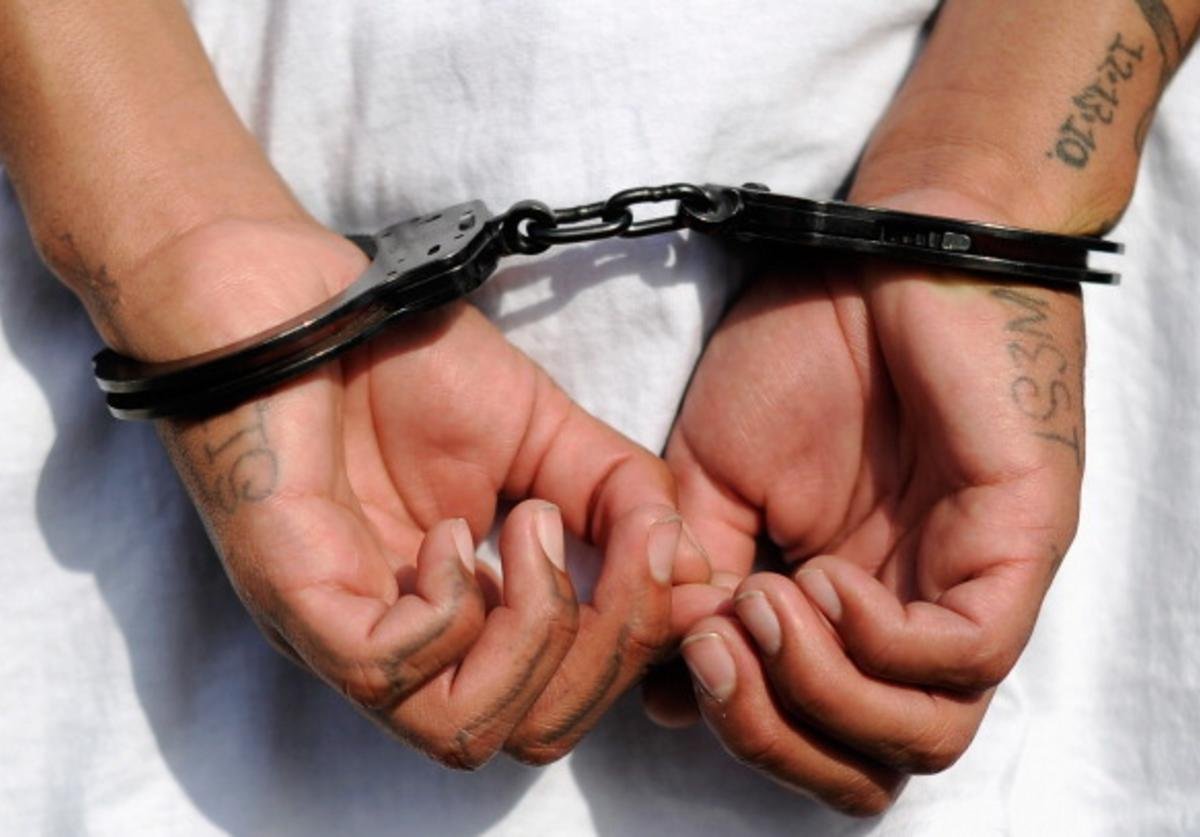 Handcuffs are seen on the hands of a twenty-year old 'Street Villains' gang member who was arrested by Los Angeles Police Department officers from the 77th Street division on April 29, 2012 in Los Angeles, California.