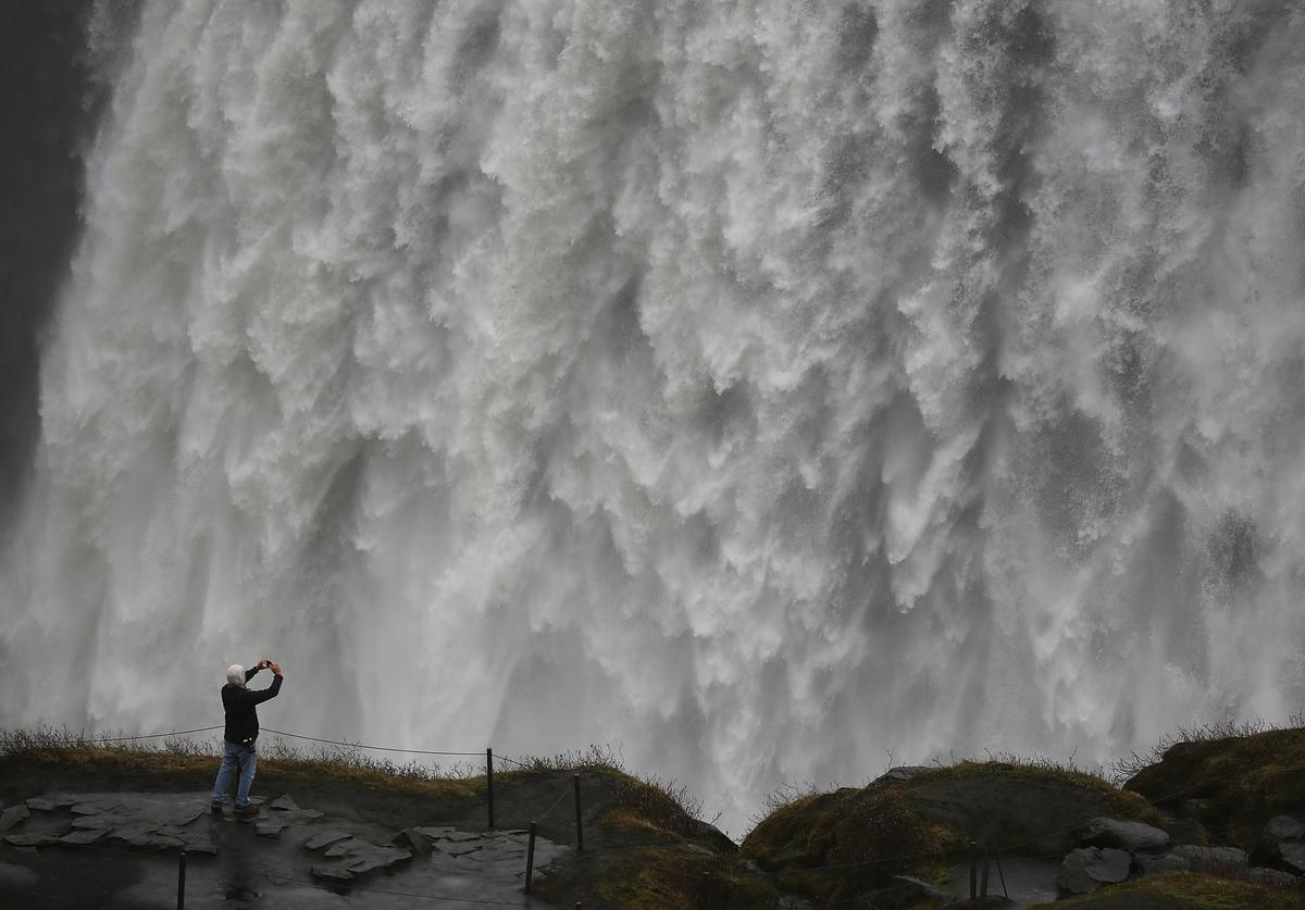 A tourist captures the scene at a waterfall known as Dettifoss on June 2, 2017 in Vatnajokull National Park, Iceland. Iceland's tourism industry continues to thrive; just eight years ago Iceland welcomed approximately 464,000 tourists and by last year nearly 1.7 million people visited the nation