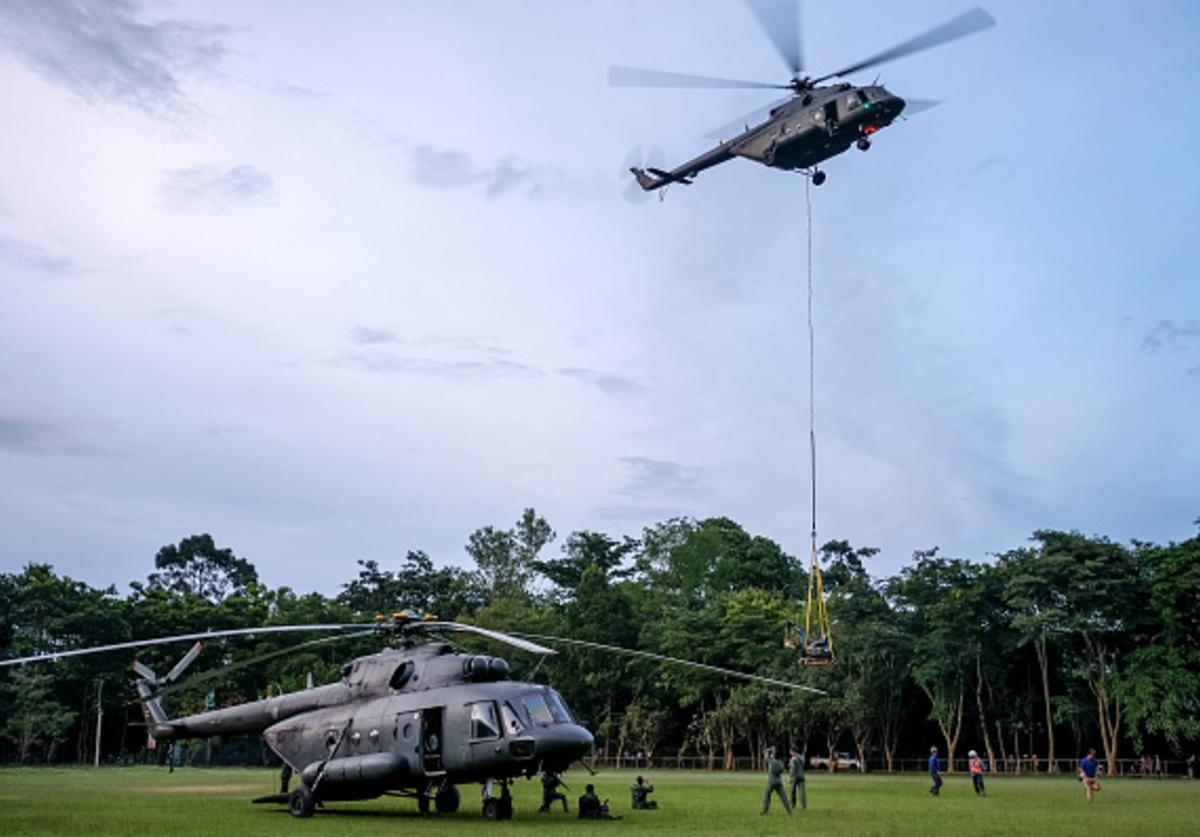 : Helicopter from Thai Airforce carry a mini excavator to the mountain top where they are trying to make a hole to get into Tham Luang Nang Non cave on July 01, 2018 in Chiang Rai, Thailand.