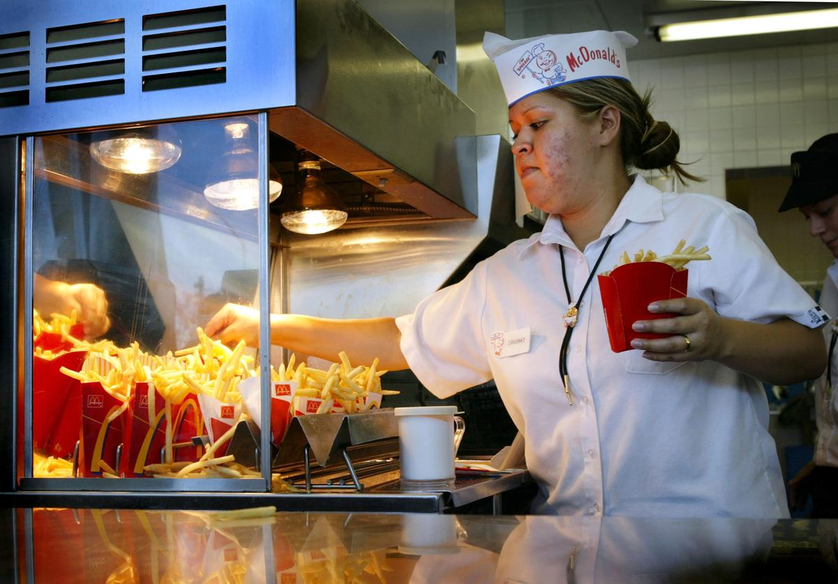 : An employee serves up french fries at the world's oldest-operating McDonald's fast food restaurant on its 50-year anniversary on August 18, 2003 in Downey, California. This 'Speedee' McDonald's, so named for the original chef logo, was the third restaurant built by the McDonald brothers Dick and Maurice and is a national landmark.