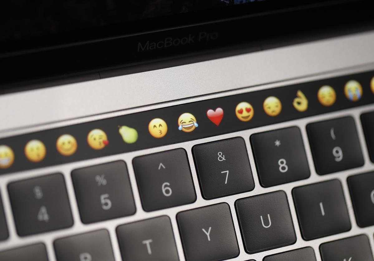 Emoticons are displayed on the Touch Bar on a new Apple MacBook Pro laptop during a product launch event on October 27, 2016 in Cupertino, California. Apple Inc. unveiled the latest iterations of its MacBook Pro line of laptops and TV app.