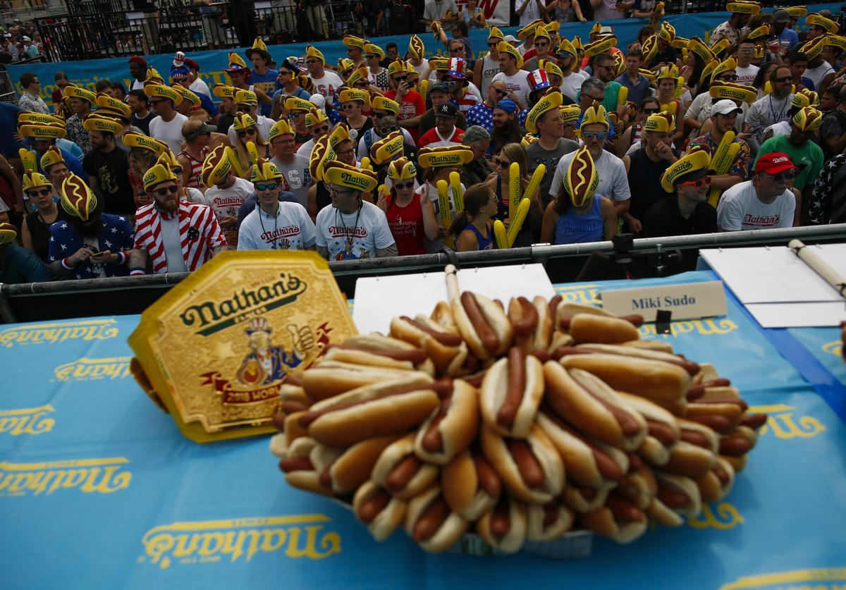 People attend the Annual Nathan's Hot Dog Eating Contest on July 4, 2018 in the Coney Island neighborhood of the Brooklyn borough of New York City. In 2017 winner Joey Chestnut set a Coney Island record eating 72 hot dogs.