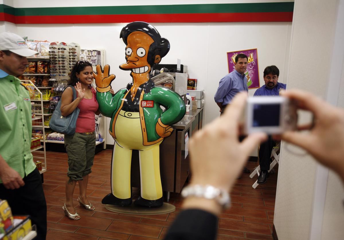 : Shelly Ramsammy poses with a representation of 'Apu,' fictional owner of the Kwik-E-Mart from the long-running televsion cartoon show 'The Simpsons' at the 7-11 store at 345 W 42nd Street, converted to a Kwik-E-Mart to promote 'The Simpsons Movie' opening next month, July 2, 2007 in New York City.