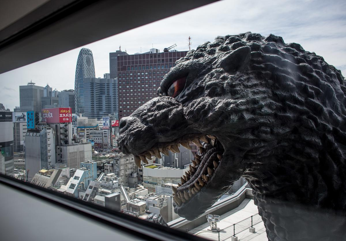A 12 meter tall Godzilla replica head is seen through a ninth floor hotel room window at the Hotel Gracery Shinjuku on April 15, 2015 in Tokyo, Japan.