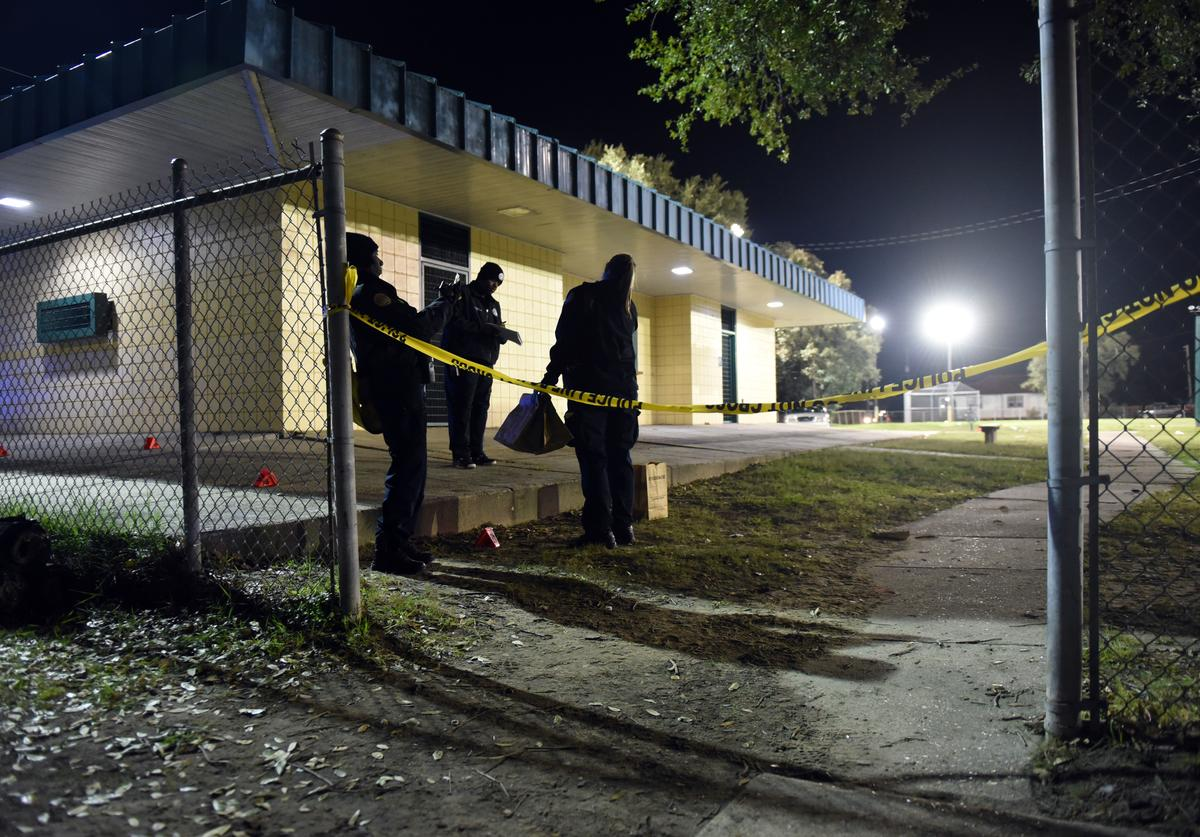 Police gather evidence after a shooting at a playground on November 22, 2015 in New Orleans, Louisiana. According to reports, as many as 16 people were shot at Bunny Friend Park while attending a party at a playground.