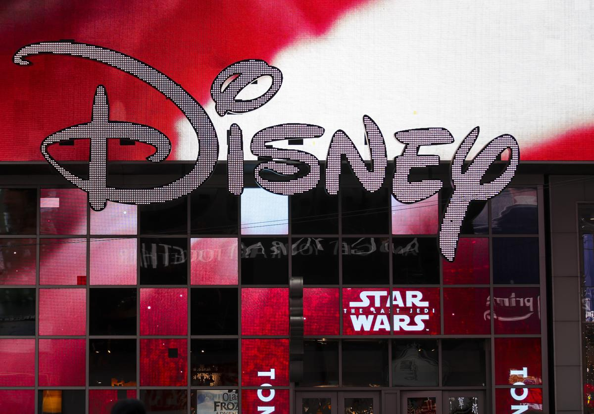 The Disney logo is displayed outside the Disney Store in Times Square, December 14, 2017 in New York City. The Walt Disney Company announced on Thursday morning that it had reached a deal to purchase most of the assets of 21st Century Fox. The deal has a total value of around $66 billion, with Disney assuming $13.7 billion of Fox's net debt.