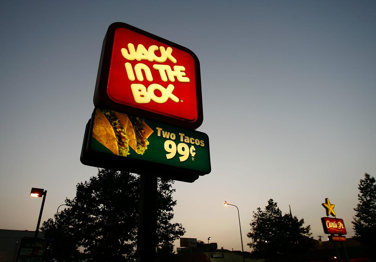 Jack In The Box and Carls Jr. fast-food restaurant signs glow July 24, 2008 on the Figueroa Street Corridor of South Los Angeles area of Los Angeles, California.