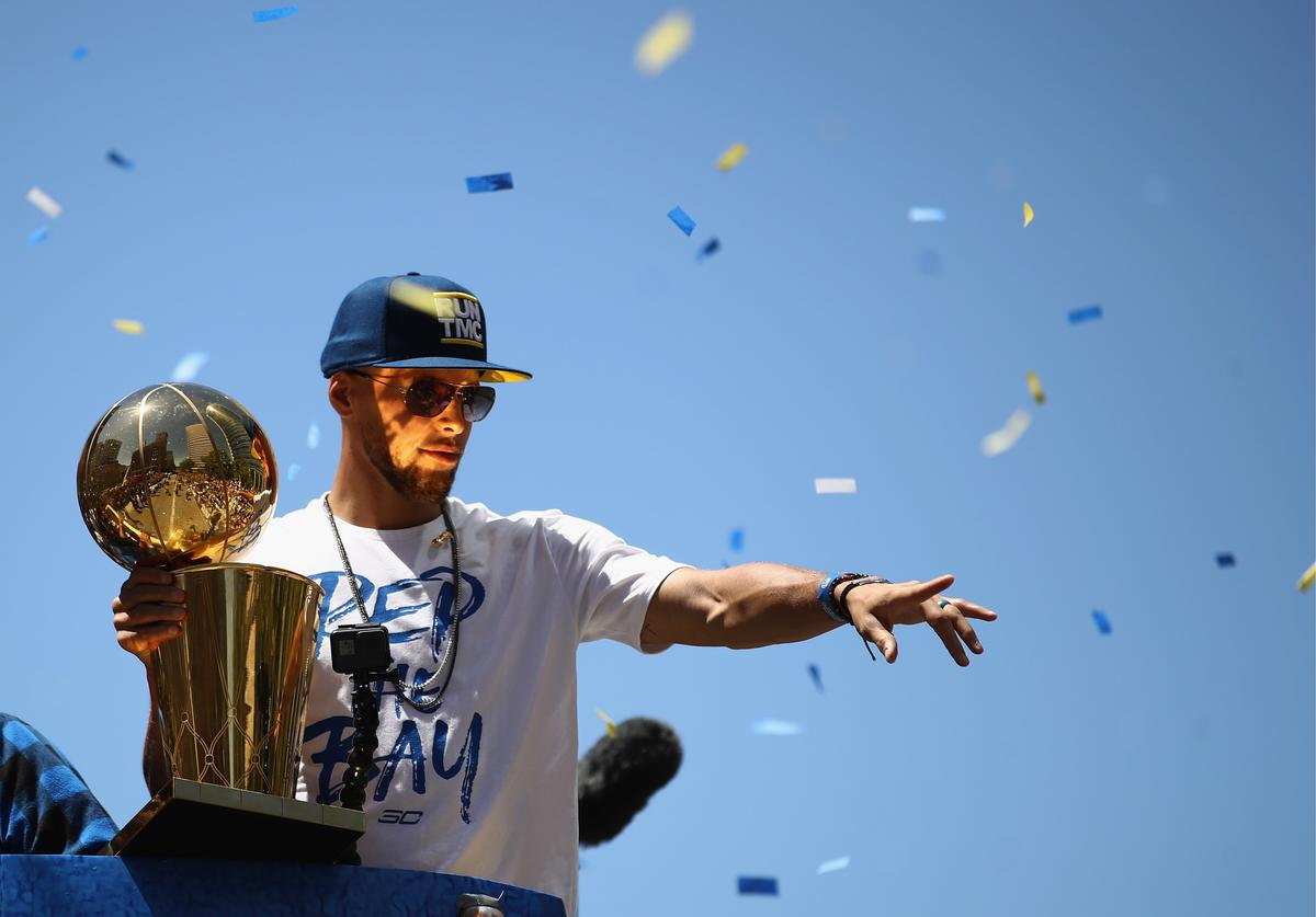 Stephen Curry #30 of the Golden State Warriors holds the championship trophy during the Golden State Warriors Victory Parade on June 12, 2018 in Oakland, California.