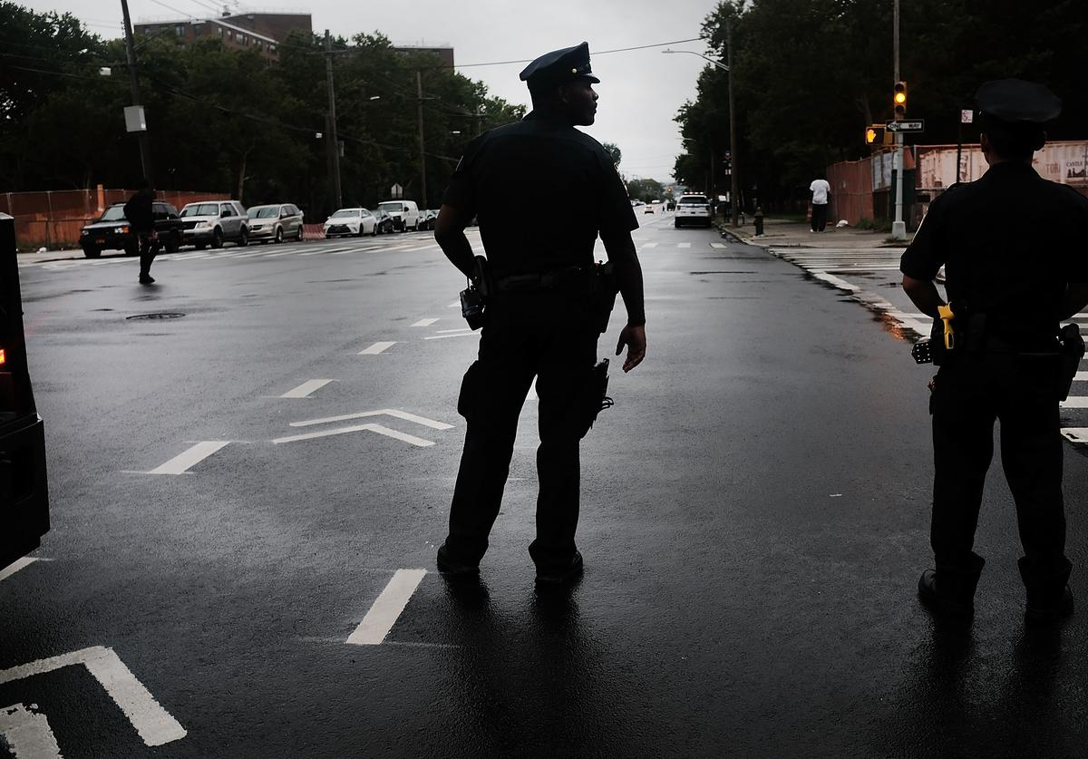 A police officer stands on patrol as people participate in a Silent Peace March against Violence in the Bronx on July 25, 2018 in New York City. Local politicians, residents, clergy members and anti-violence groups walked through the streets in silence to the location where three people were recently murdered outside of a strip mall.