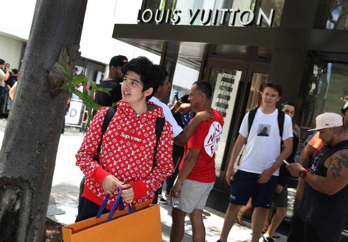 Mateo Lorente (L) wears his new Supreme shirt as people flock to the Louis Vuitton store to purchase limited edition supreme and Louis Vuitton collaboration items on June 30, 2017 in Miami, Florida.