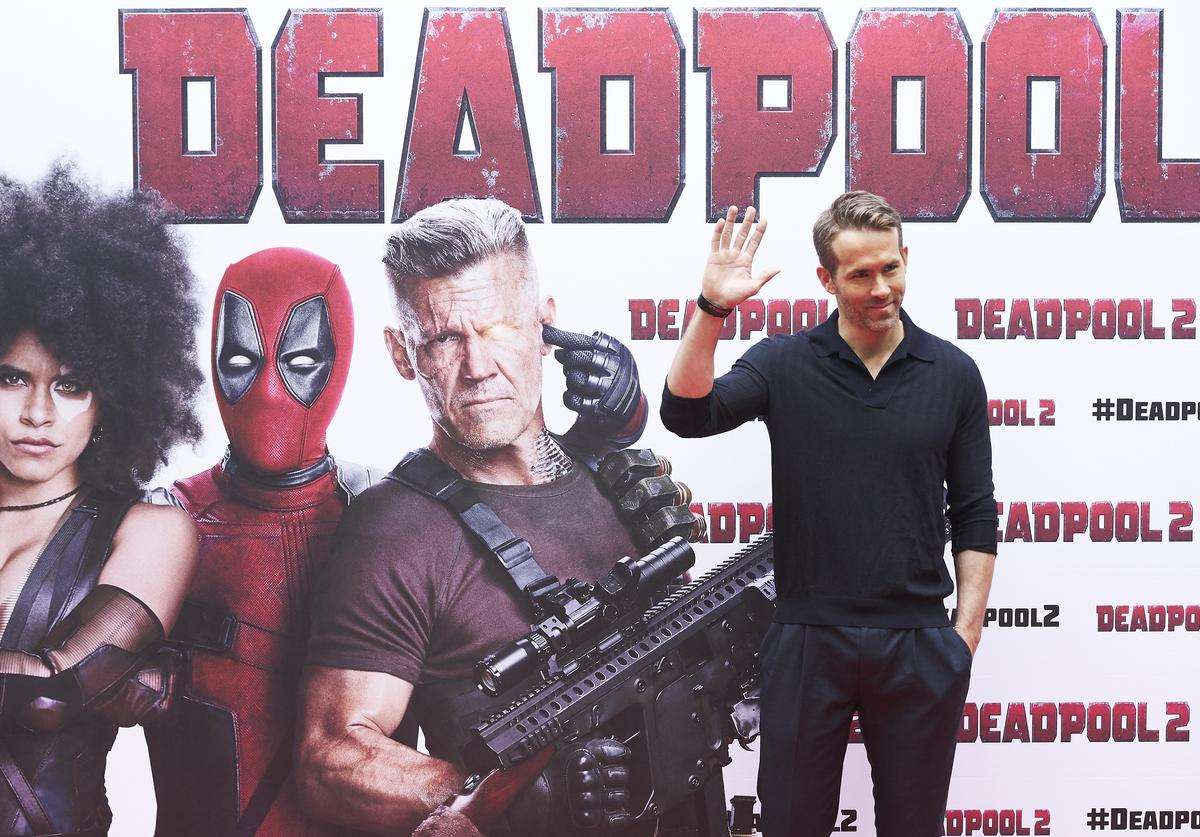 Ryan Reynolds in front of Deadpool poster