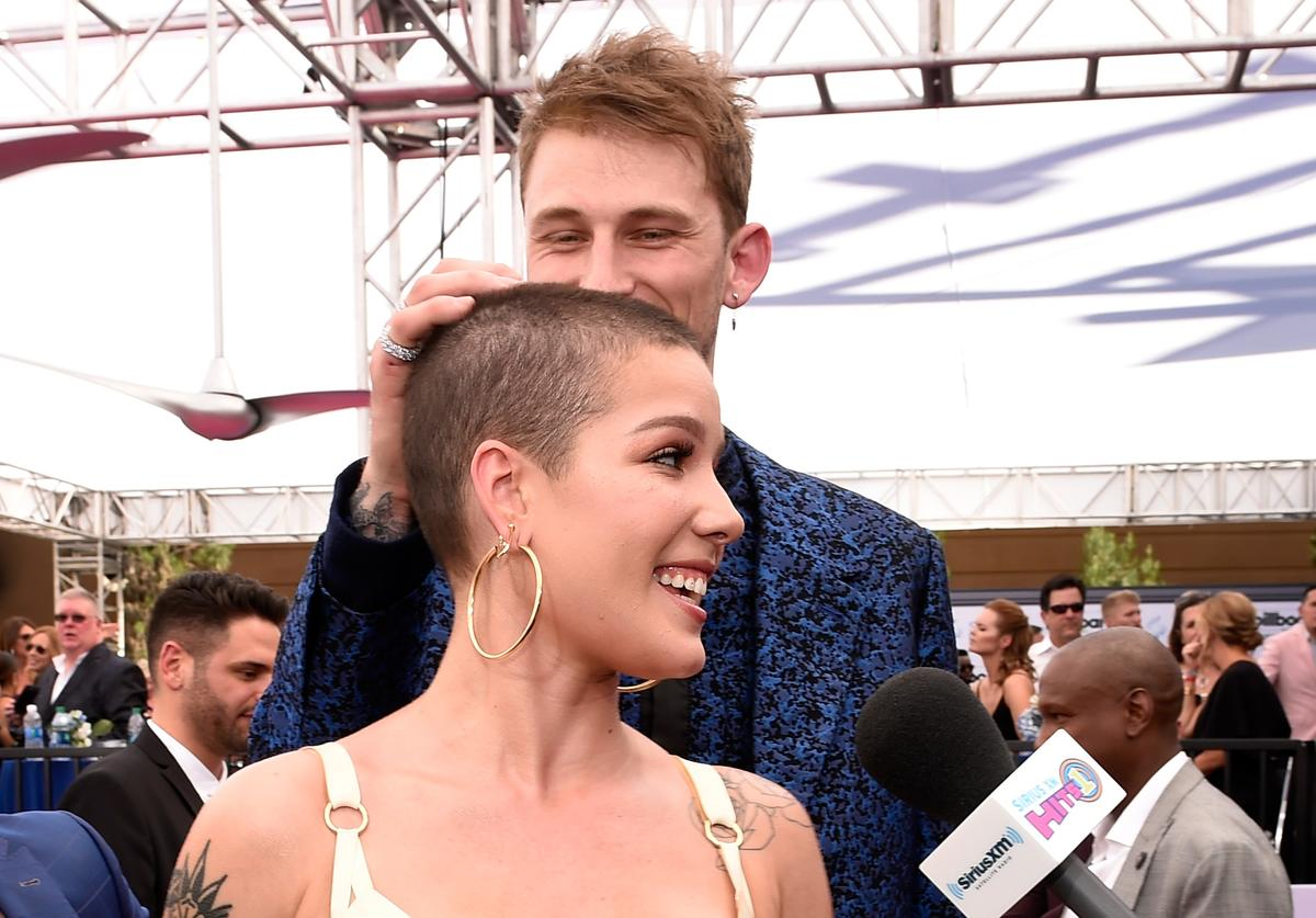 Machine Gun Kelly jokes with singer Halsey while she is interviewed by SiriusXM on SiriusXM's 'Hits 1 in Hollywood' on the red carpet leading up to the Billboard Music Awards at the T-Mobile Arena on May 21, 2017 in Las Vegas, Nevada
