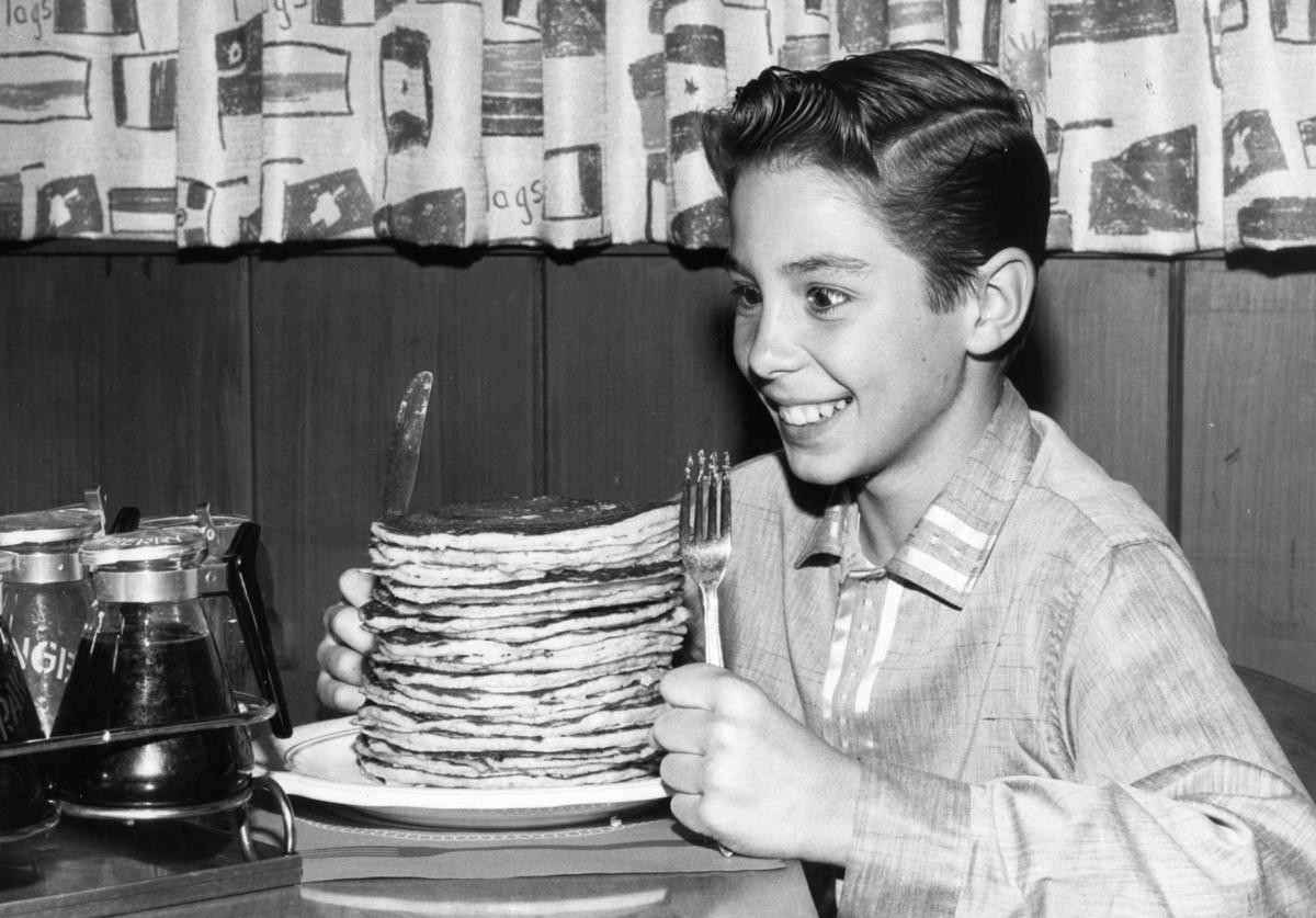 Child actor Johnny Crawford looks forward to eating a pile of pancakes in an International House of Pancakes, a chain of eateries in the USA started in 1958 by Californian brothers Al and Jerome Lapin.