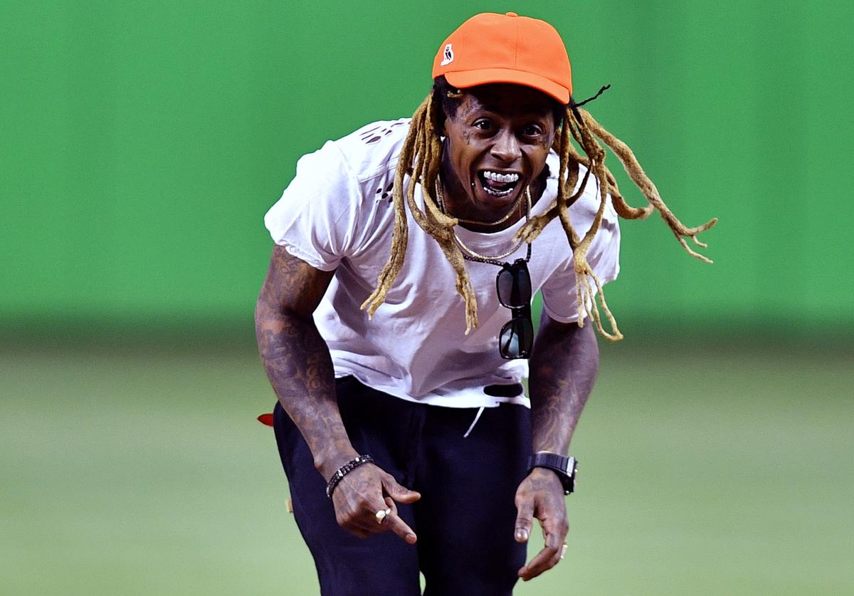 Lil Wayne laughs after throwing out the first pitch before the game between the Miami Marlins and the Washington Nationals at Marlins Park on May 25, 2018 in Miami, Florida