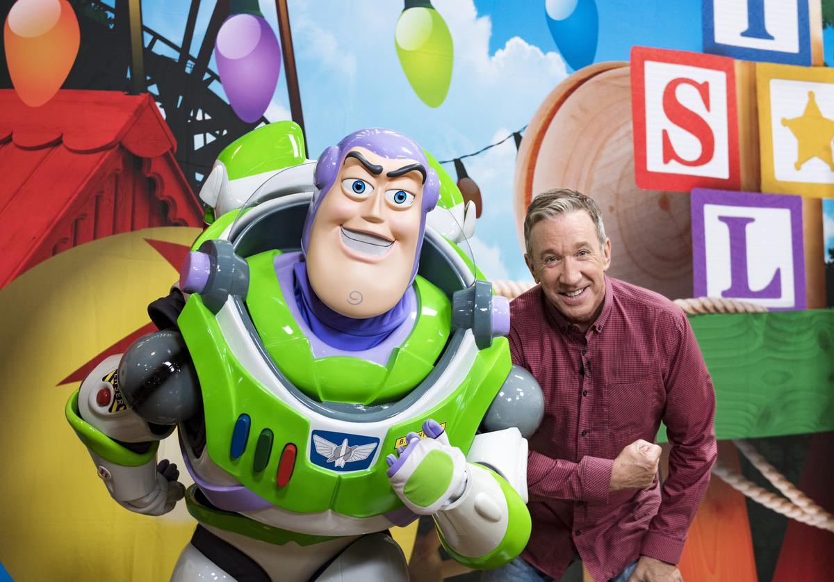 In this handout photo provided by Disney Parks, Tim Allen strikes a pose with Buzz Lightyear after taping an interview for Toy Story Land-exclusive segments with 'Good Morning America' and 'Nightline' airing on ABC, Wednesday, May 2, 2018.