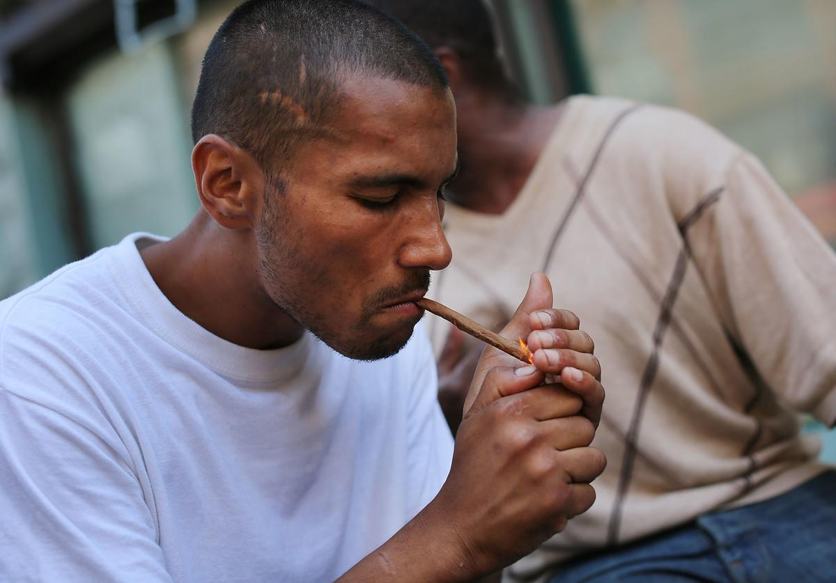 A man smokes K2 or 'Spice', a synthetic marijuana drug, along a street in East Harlem on August 5, 2015 in New York City.
