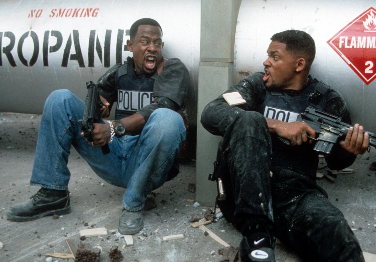 Martin Lawrence and Will Smith yelling at each other while holding machine guns to defend themselves in a scene from the film 'Bad Boys', 1995.