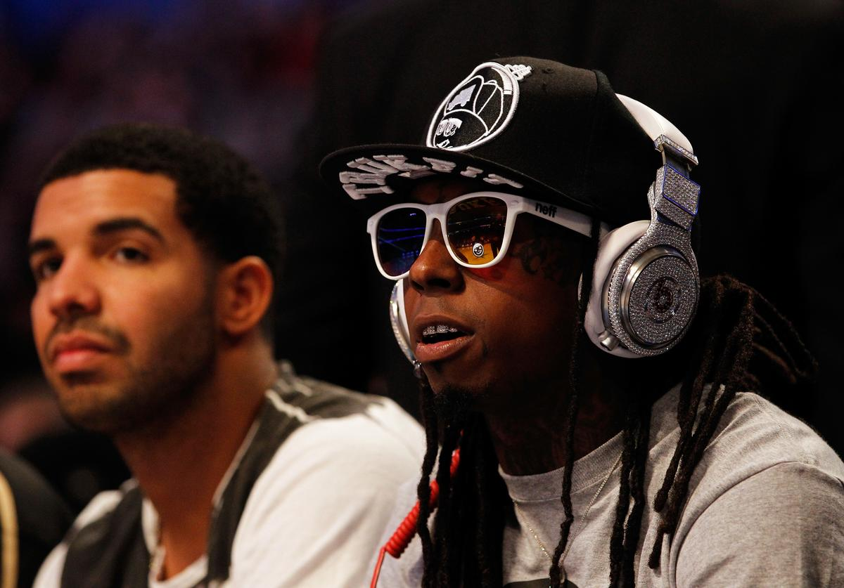 Hip-hop artists Lil' Wayne, wearing diamond studded beats headphones by Dr. Dre and Drake (L) sit courtside during the 2012 NBA All-Star Game at the Amway Center on February 26, 2012 in Orlando, Florida.