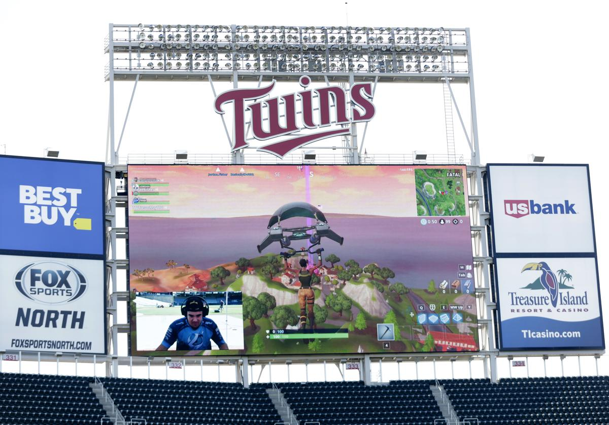 Minnesota Twins pitcher Trevor May plays the video game Fortnite with the live game projected on the stadium screen before the Minnesota Twins play the Kansas City Royals in their baseball game on September 9, 2018, at Target Field in Minneapolis, Minnesota