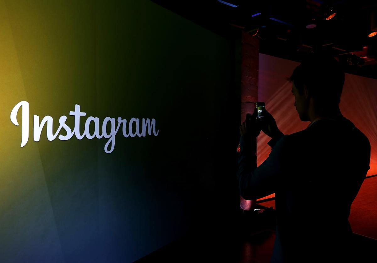 An attendee takes a photo of the instagram logo during a press event at Facebook headquarters on June 20, 2013 in Menlo Park, California