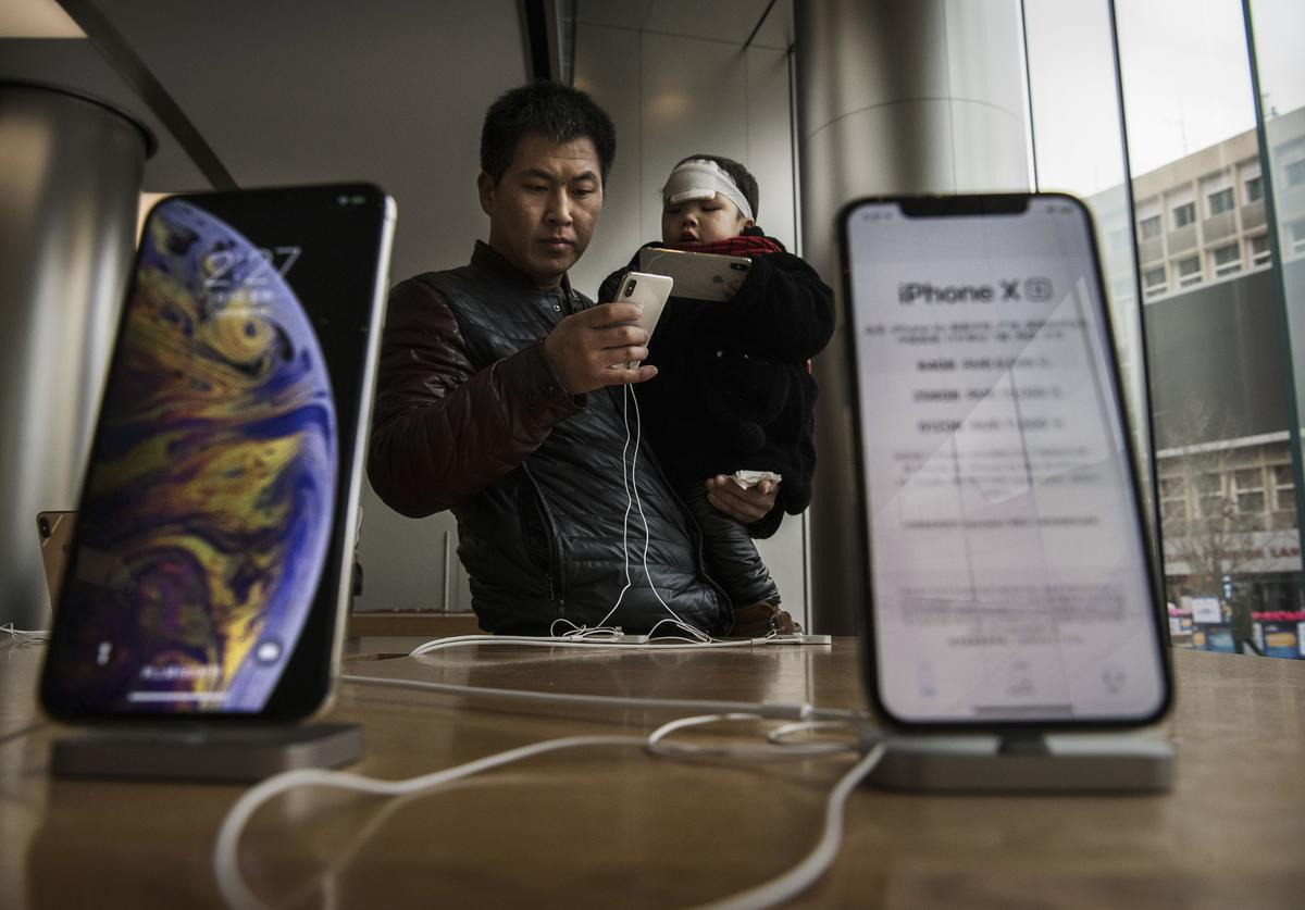 A Chinese man holds his son as they look at iPhones on display at an Apple Store on January 7, 2019 in Beijing, China.