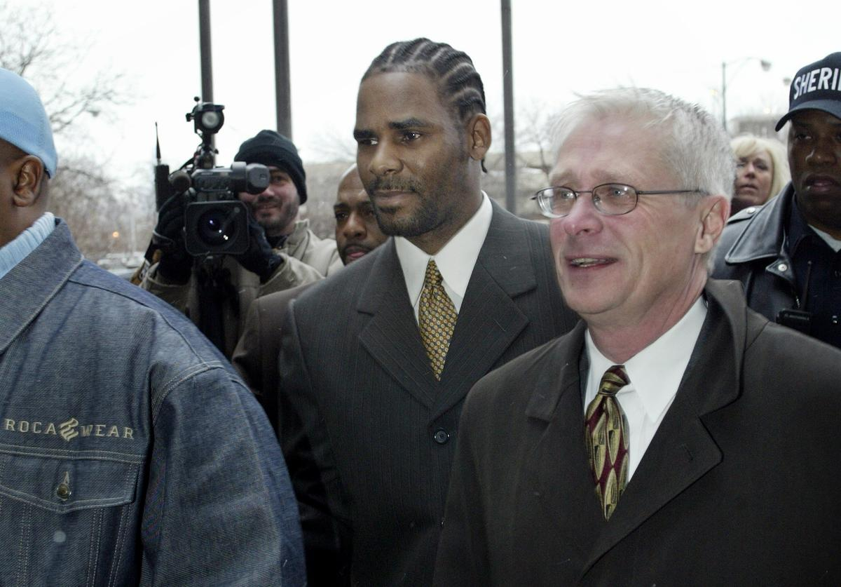 Embattled R and B singer R. Kelly (C) heads to court December 20, 2002 in Chicago, Illinois. Kelly faces 21 counts of child pornography stemming from a videotape that surfaced, allegedly depicting the singer having sex with a minor