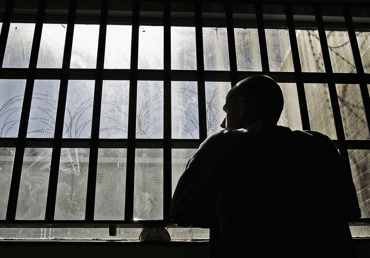 19 year old inmate James looks out of the window of the Young Offenders Institution attached to Norwich Prison on August 25, 2005 in Norwich, England.