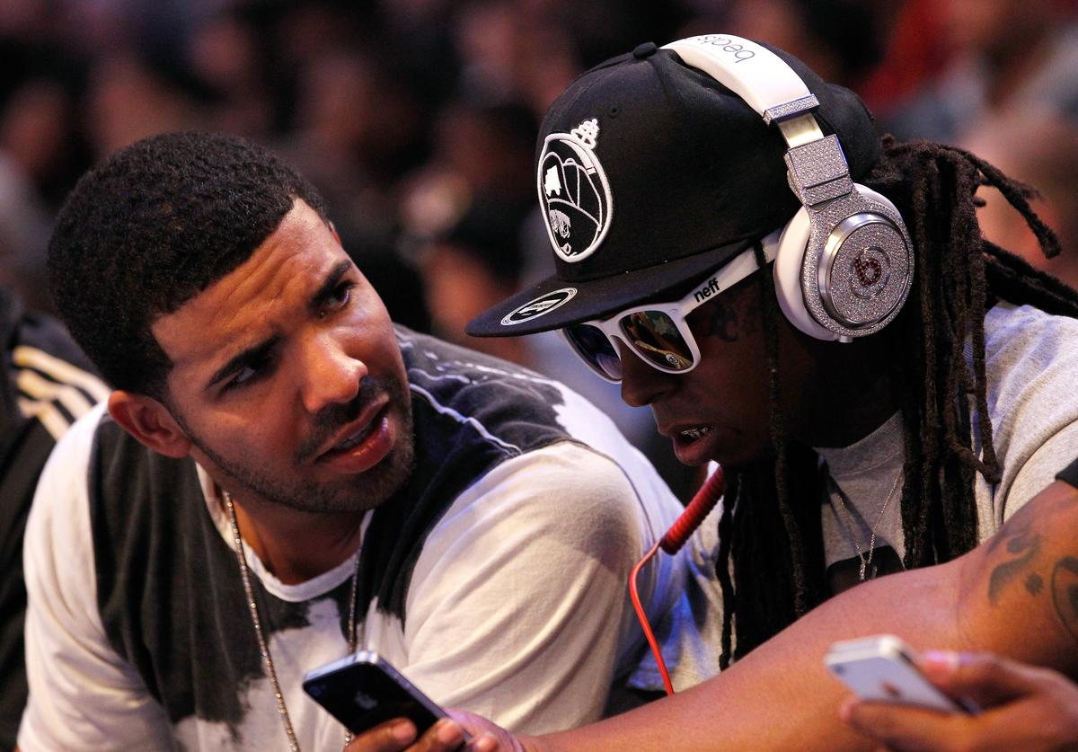 Lil' Wayne, wearing diamond studded beats headphones by Dr. Dre, and Drake (L) sit courtside during the 2012 NBA All-Star Game at the Amway Center on February 26, 2012 in Orlando, Florida