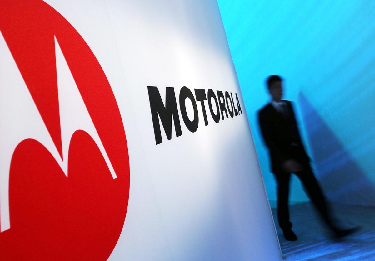 A person walks by a Motorola sign at the launch of three new Motorola smartphones under its Razr brand that will become available for Verizon customers on September 5, 2012 in New York City