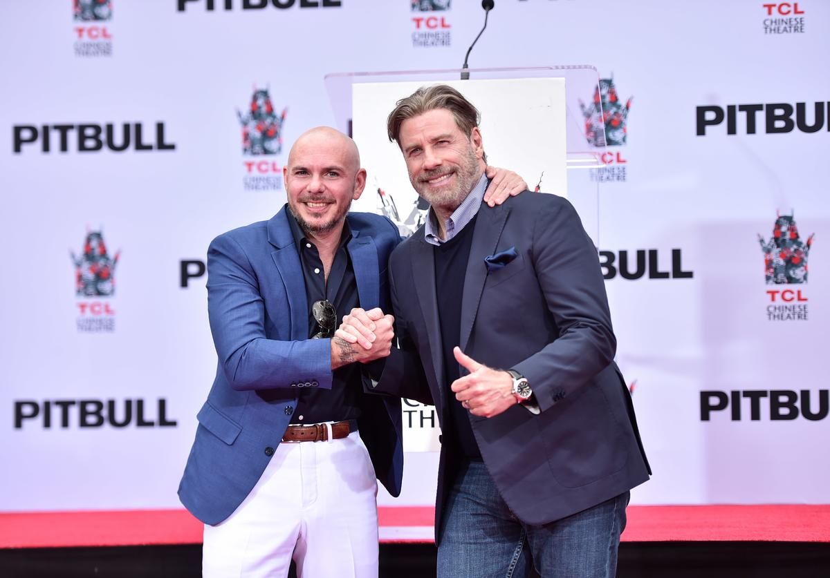 Ptibull and John Travolta attend the Hand And Footprint Ceremony Honoring Pitbull at TCL Chinese Theatre on December 14, 2018 in Hollywood, California