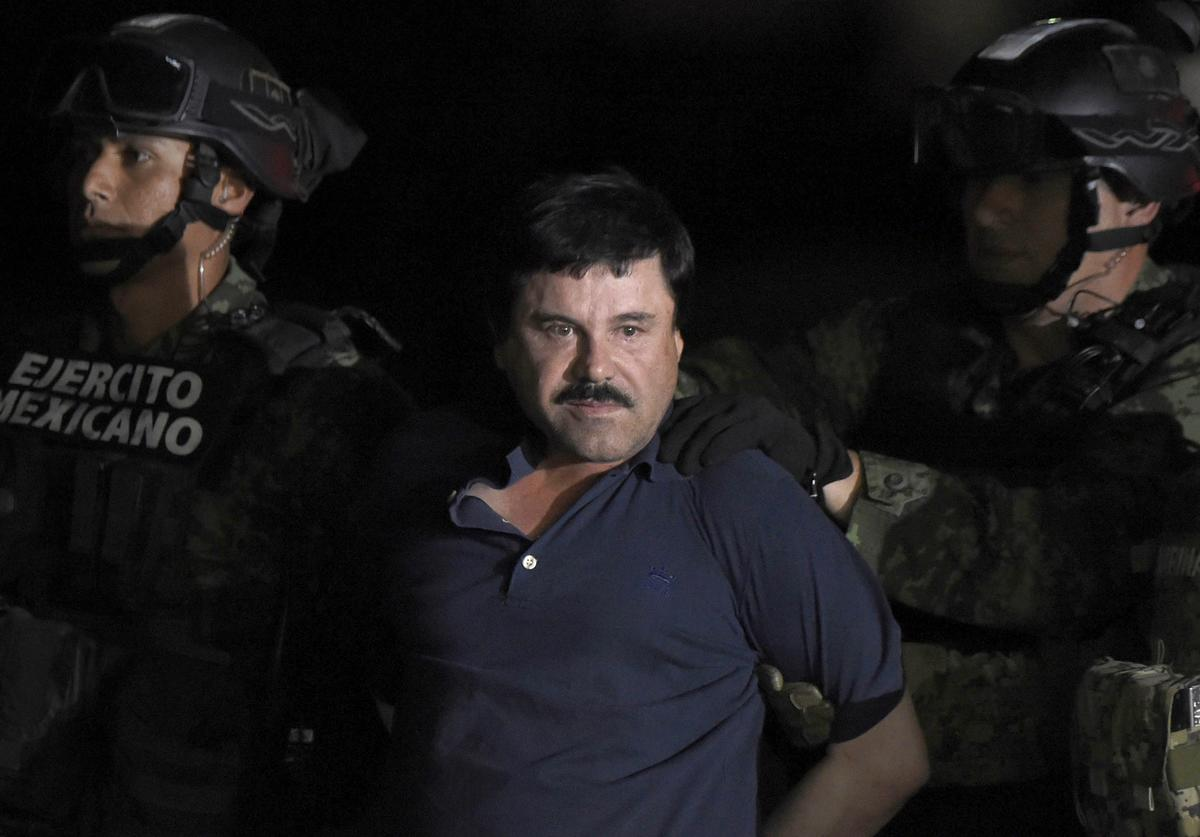 Drug kingpin Joaquin 'El Chapo' Guzman is escorted into a helicopter at Mexico City's airport on January 8, 2016 following his recapture during an intense military operation in Los Mochis, in Sinaloa State. Mexican marines recaptured fugitive drug kingpin Joaquin 'El Chapo' Guzman on Friday in the northwest of the country, six months after his spectacular prison break embarrassed authorities. AFP PHOTO / ALFREDO ESTRELLA / AFP / ALFREDO ESTRELLA