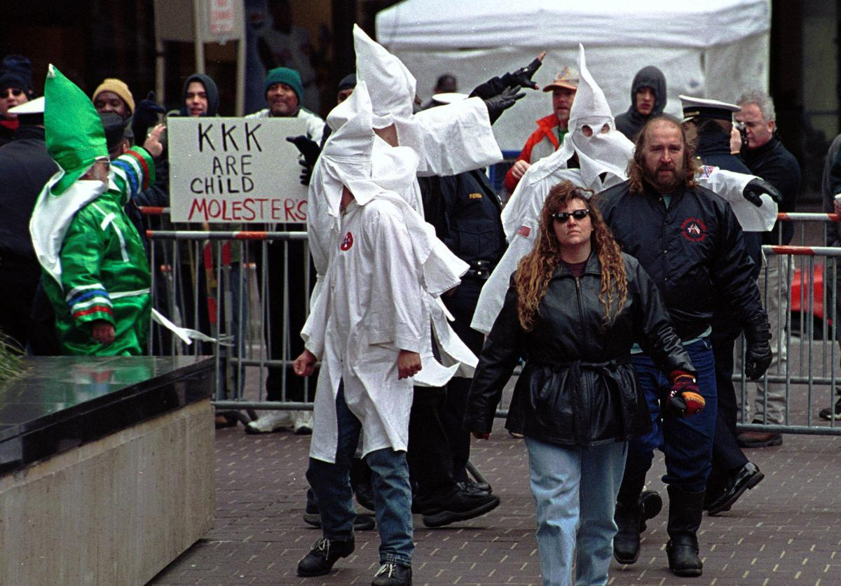 Members of the Ku Klux Klan (KKK) are yelled by anti-Klan protesters December 2, 2000 as they go to erect a cross on Fountain Square in downtown Cincinnati, Ohio. Ten KKK members put the cross up under police guard as several dozen anti-Klan protesters yelled at them. The Klan has a permit to keep the cross, which they say is a religious symbol for Christmas, on the square till December 10, 2000.