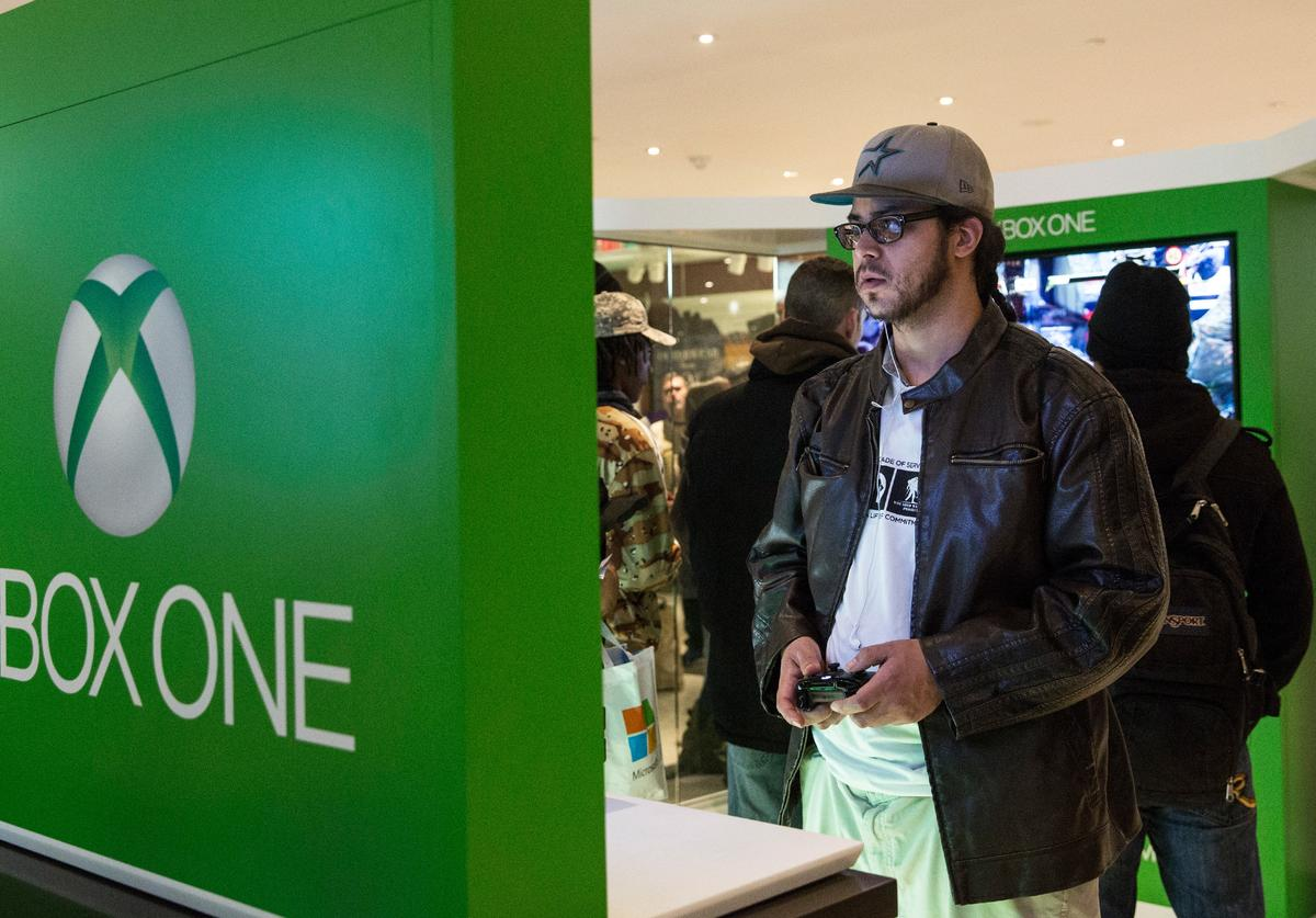 A man plays an XBox One - a new video game console and home entertainment system made by Microsoft- while waiting in line to buy an XBox One from a Microsoft 'pop-up shop' at the Time Warner Center at Columbus Circle on 22, 2013 in New York City. The X Box One arrives just in time for the holiday season, and will be competing against the Sony Playstation Four, which came out last week.