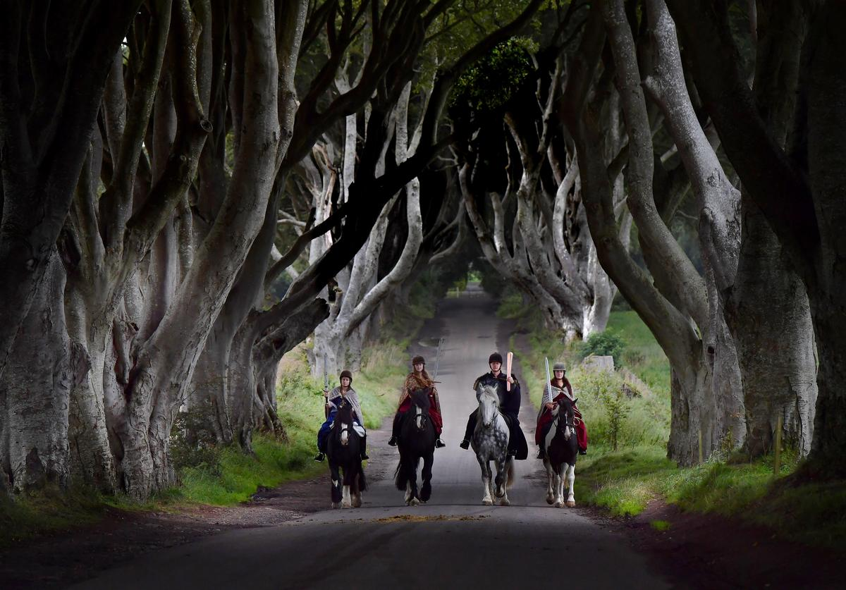 Four actors on horseback dressed in Game of Thrones related costumes carry the Queen's Baton as they make their way way along the Dark Hedges on August 29, 2017 in Antrim, Northern Ireland