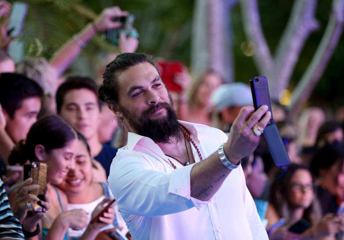 Jason Momoa takes pictures with fans on red carpet.
